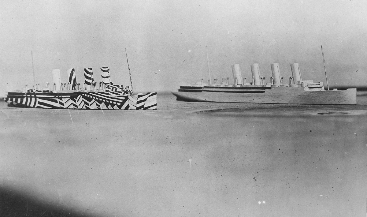 Once painted, the camouflaged ships would be placed on a tabletop to be viewed through a periscope, simulating conditions at sea, to evaluate the effectiveness of the patterns. Original caption: Models of two ships on same line of direction, one plain, and the other dazzled. This method of camouflage was used on battleships and transports to deceive U-Boat commanders and make correct aim difficult.