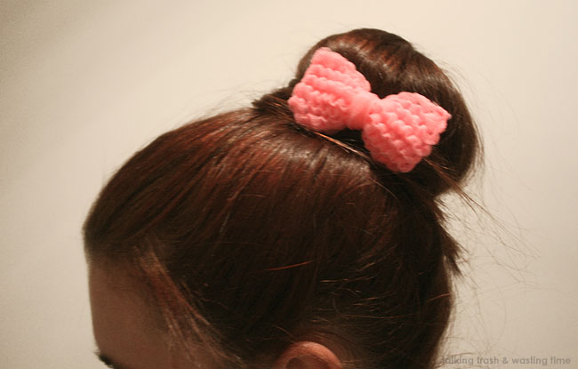 Pink hair-bow around a bun hairstyle