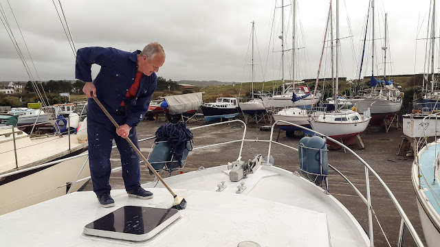 Photo of Phil scrubbing the fore deck