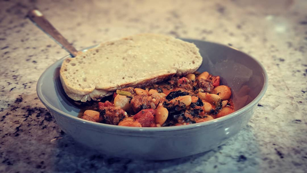 image of stew in a bowl with some buttered bread, sitting on my kitchen counter