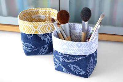 two small storage basket with blue feather pattern on the outside; one has makeup brushes in it