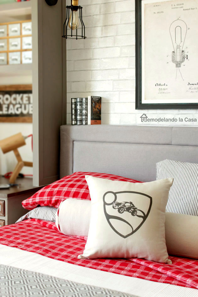 rocket League sign, pillow with Rocket league sign, uphostered bed, white brick wallpaper