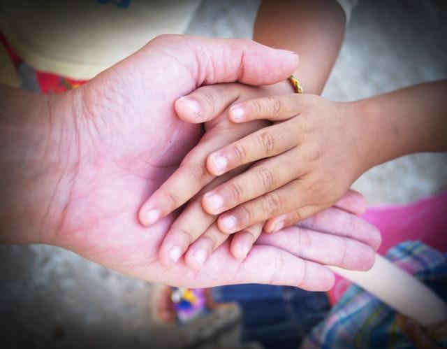 Manos entrelazadas de dos niños y un adulto