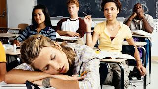 Schoolgirl sleeping in classroom