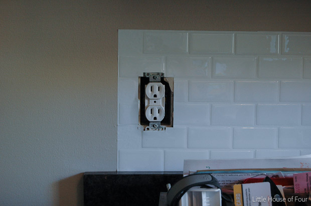 Adding peel and stick tiles around electrical outlet