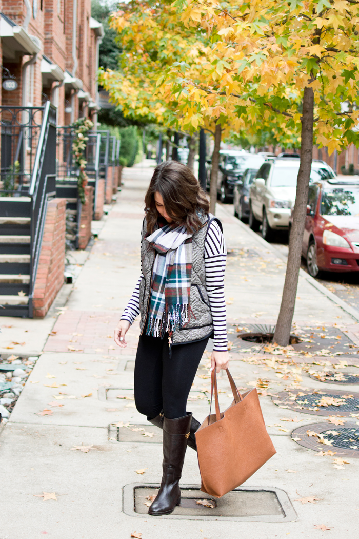 casual christmas outfit idea with tory burch riding boots and jcrew vest