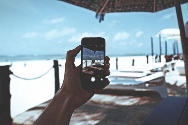 Homem fotografa praia em viagem a outro pais usando chp de internet no exterior