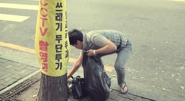 Coreano tirando la basura en la calle de forma ilegal