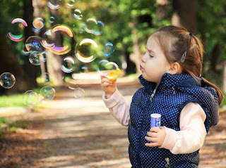 This is a picture of a girl blowing bubbles
