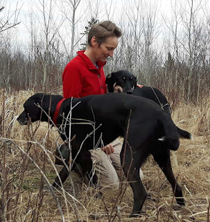 Photo of Kristi Benson with two of her dogs in a field