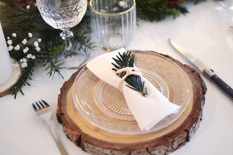 verre à vin Villeroy et boch, verre à eau H&M Home,rondin de bois, assiette en verre maisons du monde, serviette blanche et branche de sapin