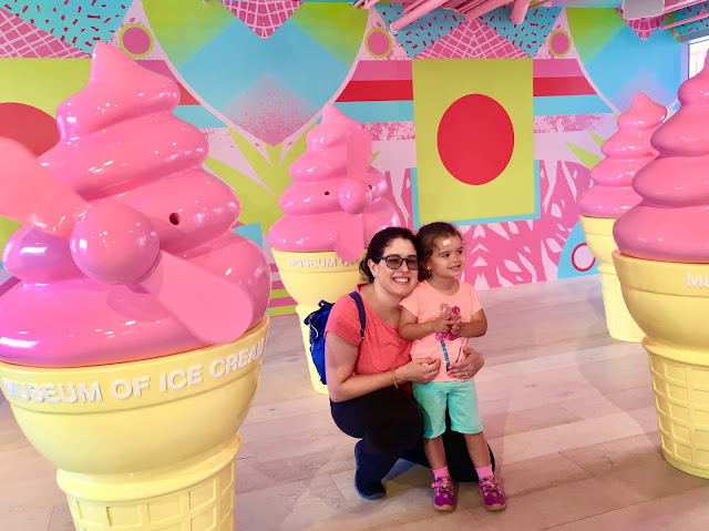 Ice cream in a cone shaped windmills and mother and daughter posing for a photo