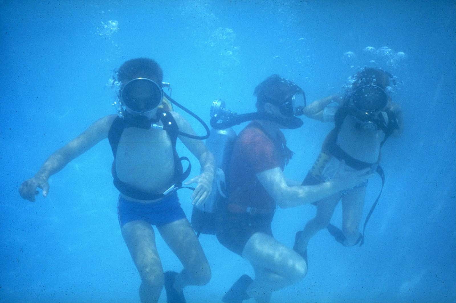Neil Armstrong and his sons, Ricky and Mark, scuba dive in a swimming pool in Houston, Texas, in March 1969.