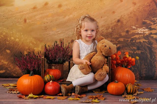 Jesienna sesja rodzinna z dzieckiem w studio dynie liście i misio uśmiechniętego dziecka