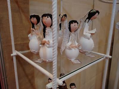 Fotografia colorida. Cinco bonecas de cabelos pretos, vestidas de branco, em uma vitrine.