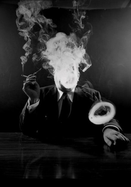 Man in suit, face obscured by cigarette smoke