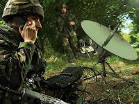 Cephede bir muhabere eri çanak antenli bir uydu telefonuyla konuşurken