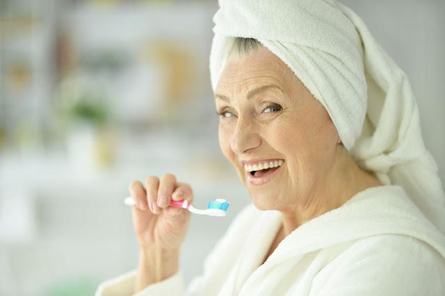 starsza kobieta myjąca zęby