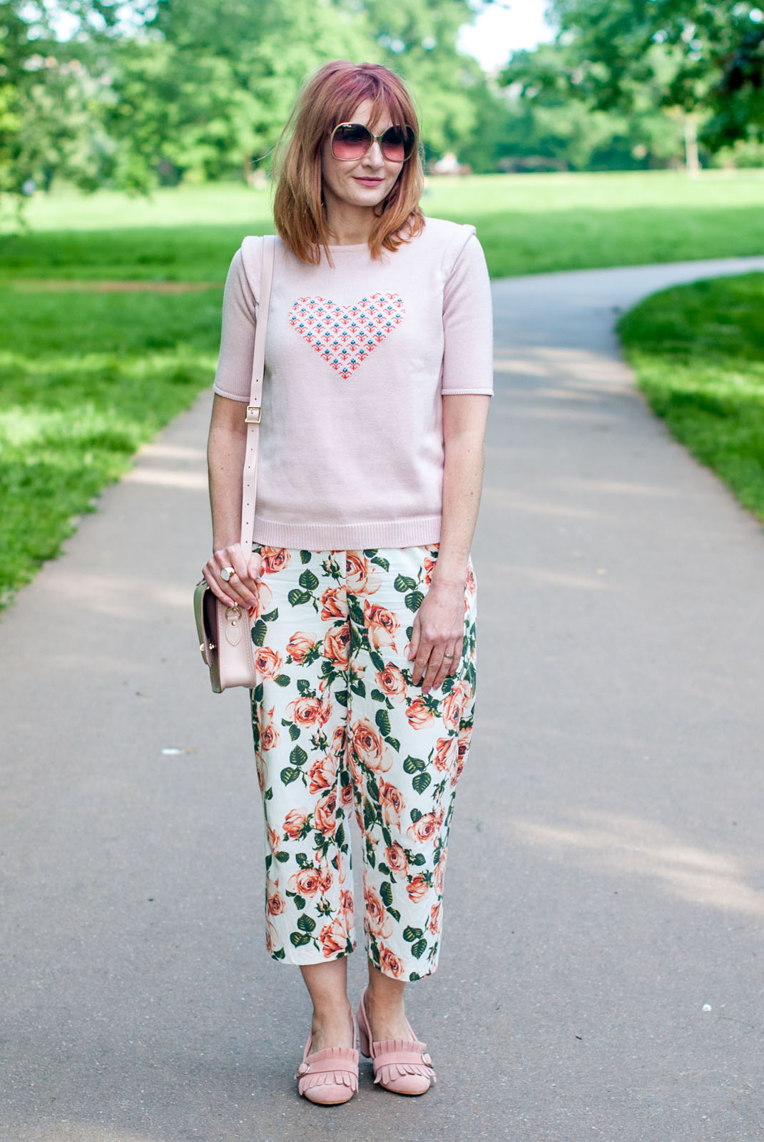 Blush pink summer outfit: Pink sweater with heart motif \ cropped floral trousers pants \ blush pink suede Gucci-style heeled loafers \ pink satchel | Not Dressed As Lamb, over 40 style