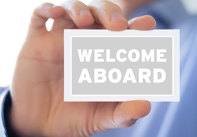 hand holding a card that says welcome aboard