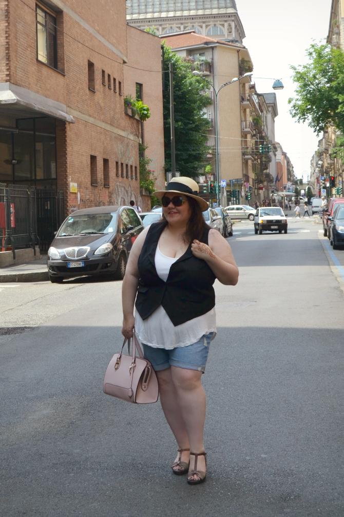 outfit plus size con shorts in denim strappati, gilet nero, canotta bianca e panama