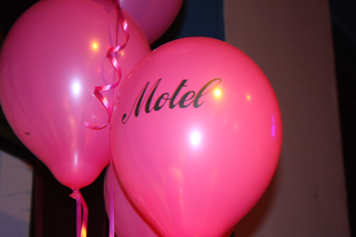 a hot pink helium balloon with the word 'motel' printed on the side with their logo