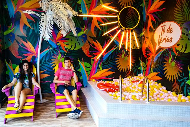 Casal sentado em cadeiras coloridas , uma piscina de bolinhas na direita