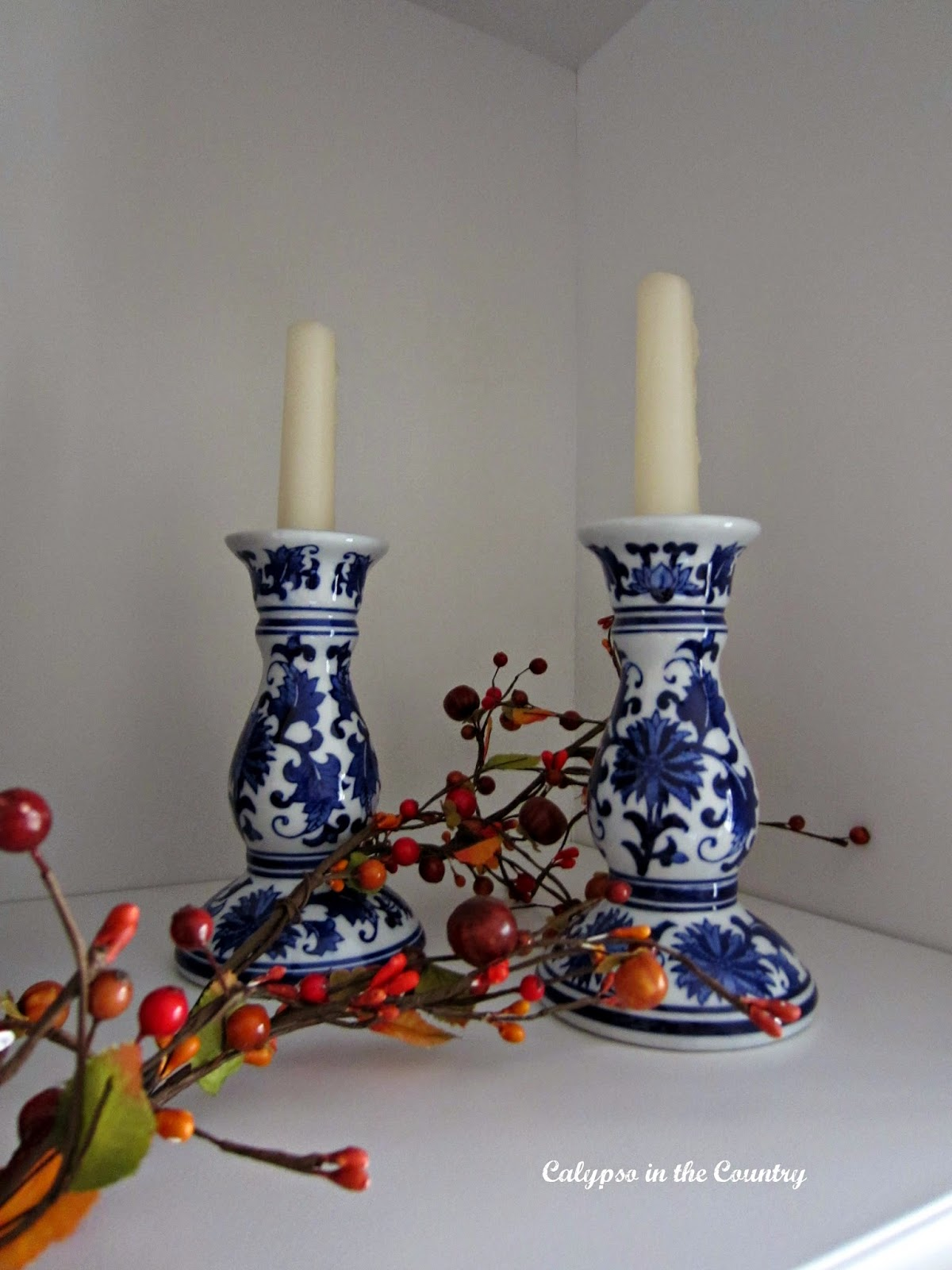 Blue and white candlesticks on white bookshelf decorated for fall
