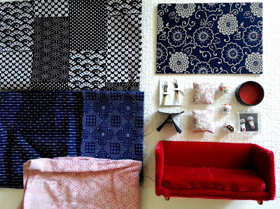 A flat lay with three pieces of blue and white Japanese-patterned fabric (and one in red), a card with a piece of blue and white japanese fabric on its front, a deep red miniature velvet sofa, a one-twelfth scale Yanagi butteryfly stool, three one-twelfth scale lucky cats, two one-twelfth scale cherry-blossom cushions, a pair of one-twelfth scale slippers and two pairs of one-twelfth scale chop sticks. All on piece of white woven wallpaper.