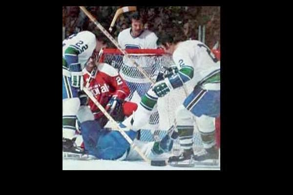 Doug Mohns with Canucks to the right, left, behind & below