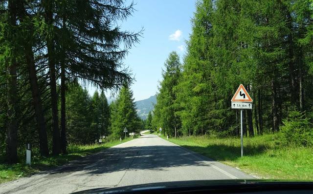 Fahrbahn umgeben vom Wald und Straßenschild auf der Großen Dolomitenstraße