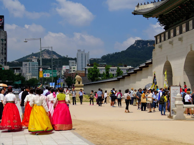 Visitors in period costume outside Gyeongbokgung Palace in Seoul South Korea