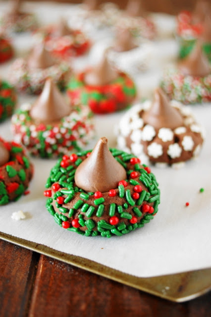 Spread some holiday cheer with these adorable little Christmas Chocolate Kiss Cookies. They're a great cookie project for grown-ups and kids alike because they're just plain fun to make ... and to eat!