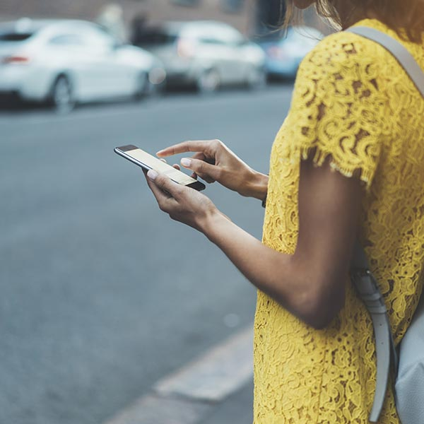 woman searching phone on street