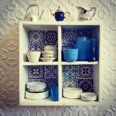 Modern miniature white wall shelf with blue and white tiles on the back, filled with blue and white crockery and with various jugs displayed on the top.