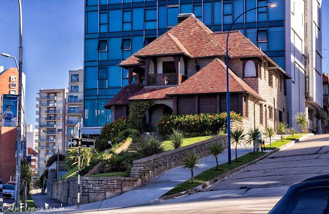 Chalet en esquina contrastando con edificio moderno a sus espeldas.