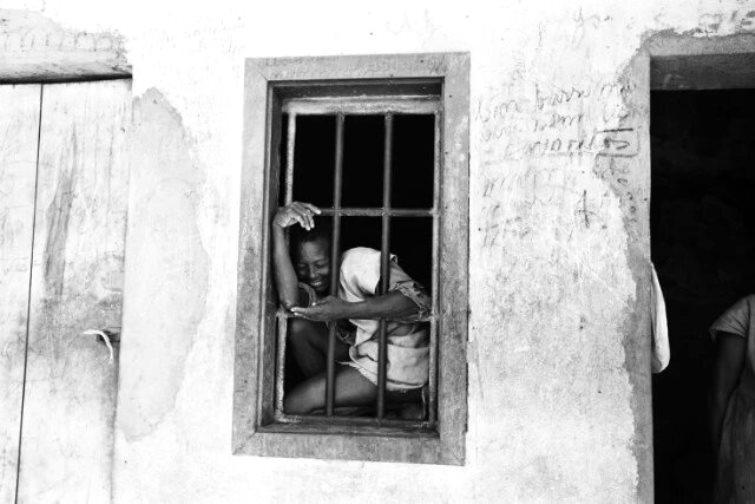 Foto de Luiz Alfredo do Colônia, com uma mulher à grade da janela