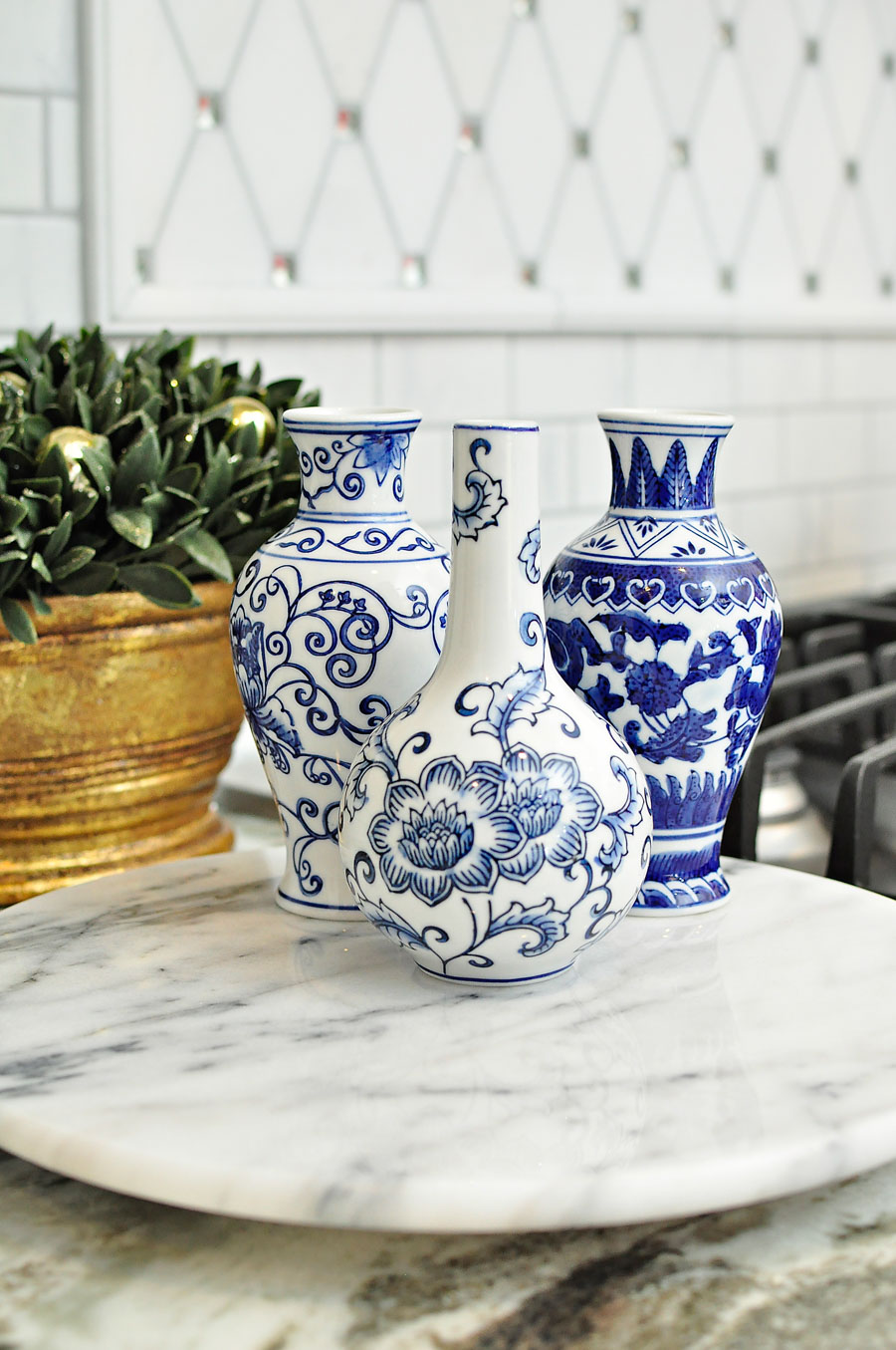 Mini blue and white ginger jar vases on a marble lazy susan in an all white kitchen.