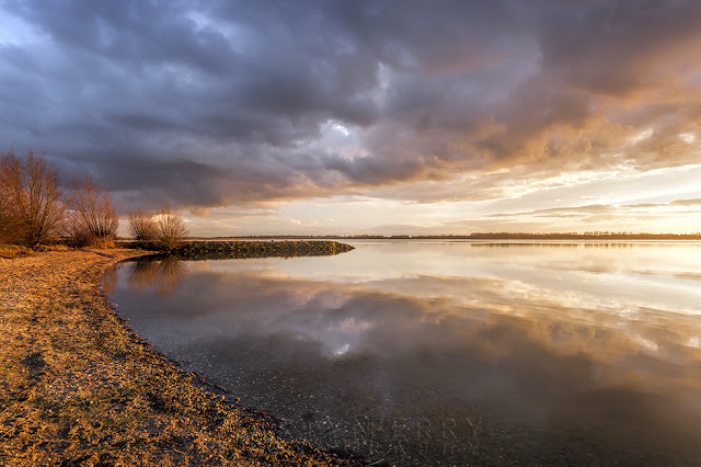 Beautiful sunset colour in the clouds reflects in Grafham Water reservoir