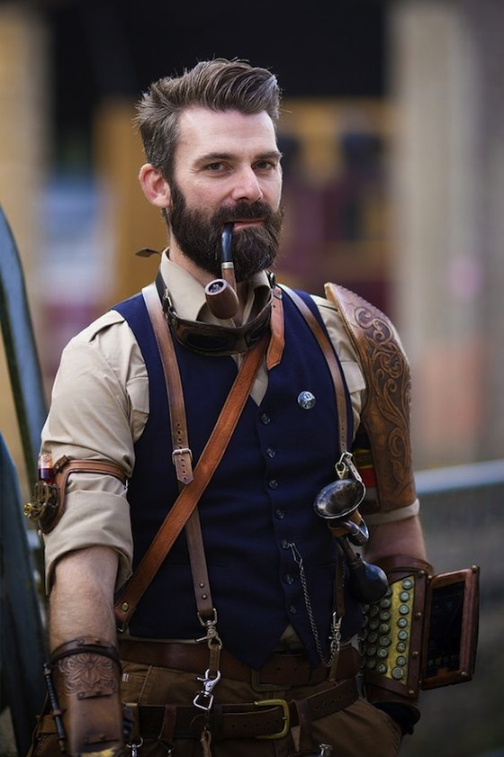 Man in steampunk clothing in brown and navy blue. utility belt, pipe, gauntlet, accessories. Men's steampunk clothing and costumes