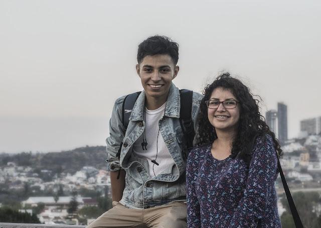 una pareja latina tomandose fotografia cerca de la ciudad