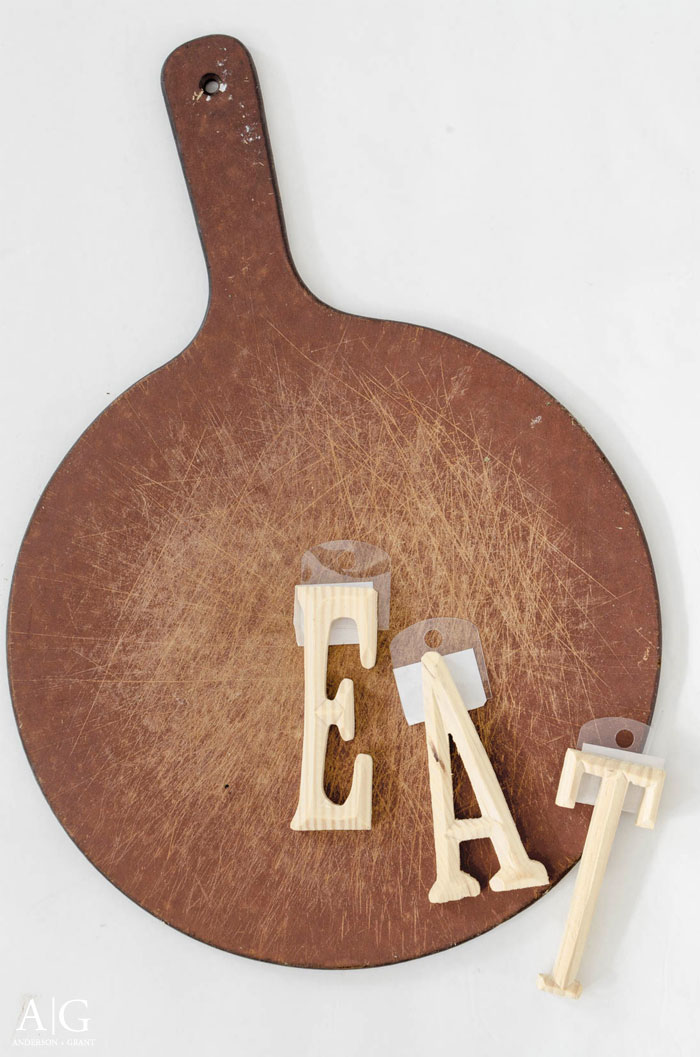 An old pizza board and some unfinished letters from Michaels are transformed into some rustic kitchen decor.