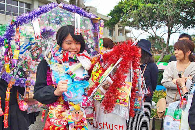 girl, umbrella,toys, leis,candy,uniform,parent,smiles