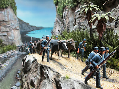 Diorama of 19th-century soldiers walking along a track near the sea.