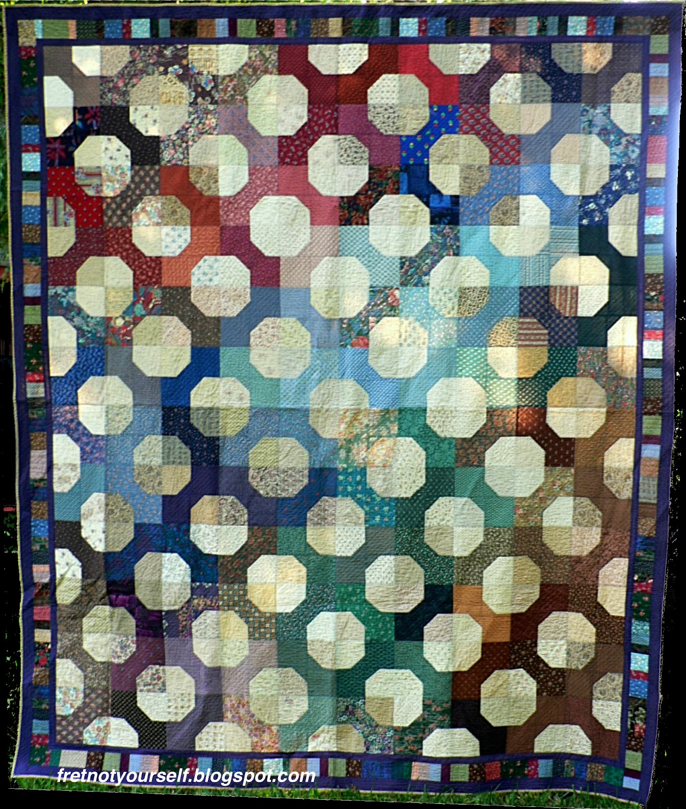The Bow Tie blocks are grouped by similar colors across the surface of this queen-sized quilt.