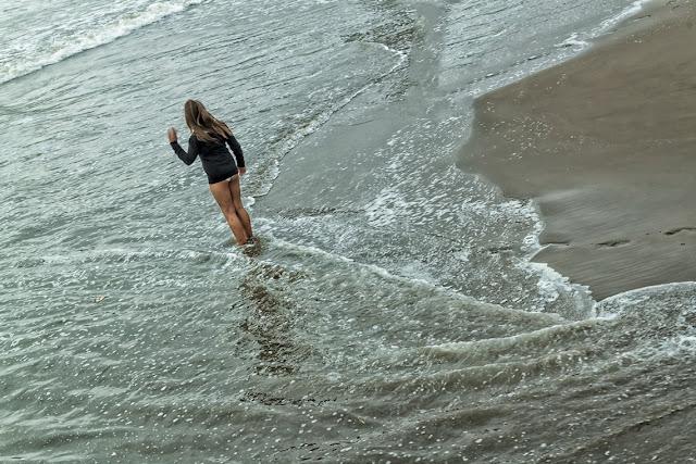 Joven con malla y un pullover pies en el mar