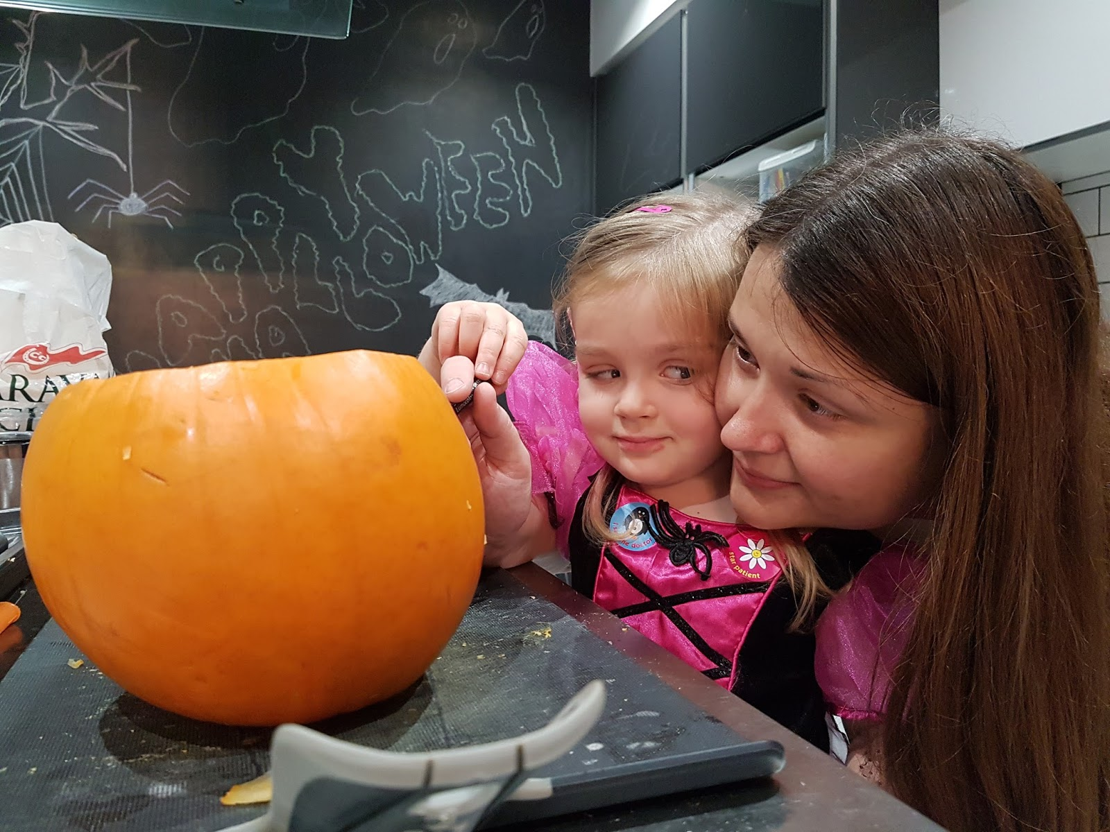 mother and daughter carving pumpkins