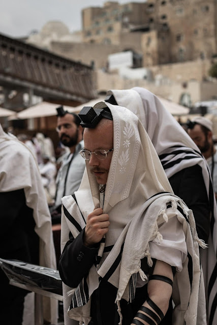 A praying Jew covered in his tallit and wearing tefillin