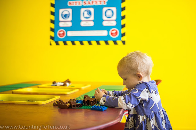 Building with LEGO style blocks at 360 Play in Basildon in front of a bright yellow wall and sitting at a table with yellow boxes of LEGO