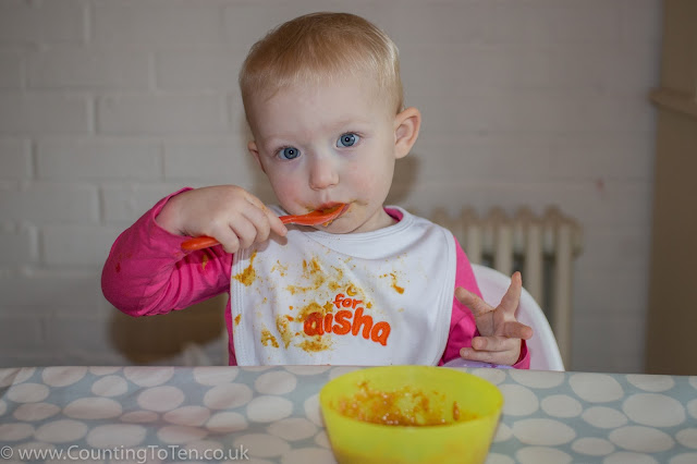 A toddler pondering on the taste of some food she is eating and which is all over her white cotton bib as well